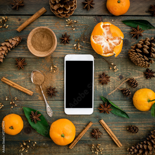 Christmas or New Year concept with smartphone, citrus fruits, pine cones and cinnamon on wooden background. Flat lay, top view. - 177394514