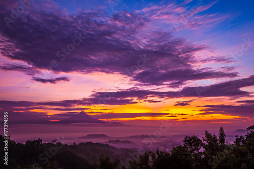 Fotobehang Crimson Mysticism and fog during sunrise over Candi Borobudur. Incredible colorful clouds of pink, the sky is yellow in blue. Sunrise in Jawa Tengah, Indonesia. View of Gunung Merbabu.