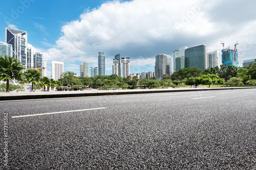 empty asphalt road and modern buildings in midtown of modern city Poster