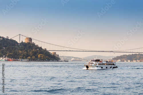 A beautiful luxury yacht runs along the waters of the Bosphorus against the bac Poster