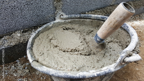 Fototapeta lay bricks with cement mixing tub, mortar concrete