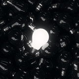 Single self illuminated light bulb on a pile of dead black light bulbs. - 177421525