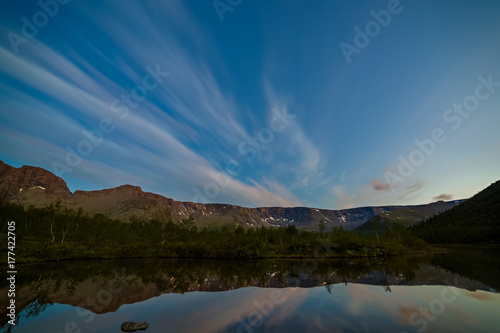 The sky with the stars at dawn, reflected in the water of a mountain lake Poster
