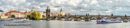 Prague, Czech Republic - October 12, 2017: Dramatic cloudy panorama of Charles Bridge, Vltava river, Prague Castle and Old Town, Prague, Czech Republic. Panoramic autumn view of Prague.