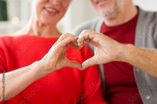 Leinwanddruck Bild close up of senior couple showing hand heart sign