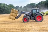 Schwarzer Traktor transportiert Strohballen, Seitenansicht