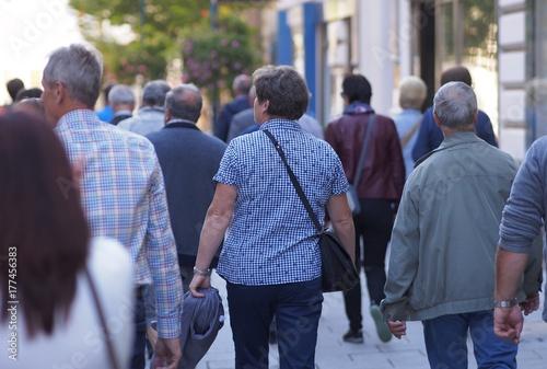Gruppe von Touristen flaniert durch eine Geschäftsstraße Poster