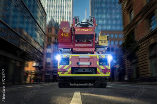 Wóz strażacki z antenową drabiną jedzie przez miasto