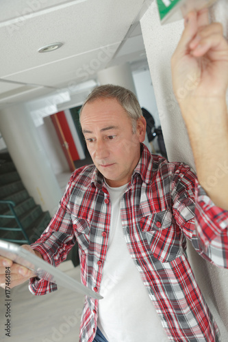 Man testing security exit light Poster