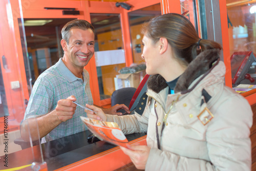 Woman buying ticket through hatch - 177468101