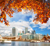 London with modern city against autumn leaves in England, UK