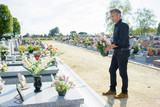 Man by graveside holding pot of flowers