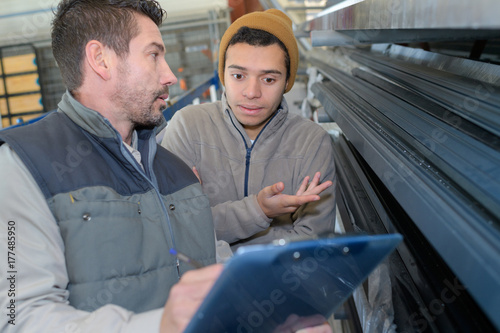 male engineer with apprentice checking stock levels Poster