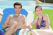 Portrait of man and lady sat on sun loungers
