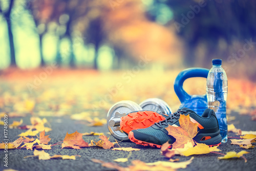Fototapeta Pair of blue sport shoes water and dumbbells laid on a path in a tree autumn alley with maple leaves - accessories for run exercise or workout activity