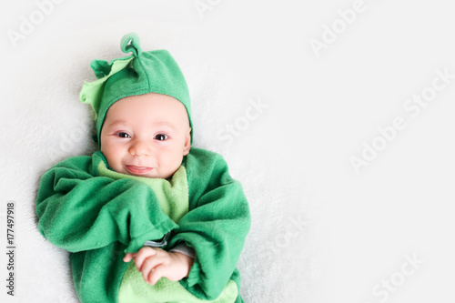 Baby dressed up in a dinosaur costume for Halloween Poster