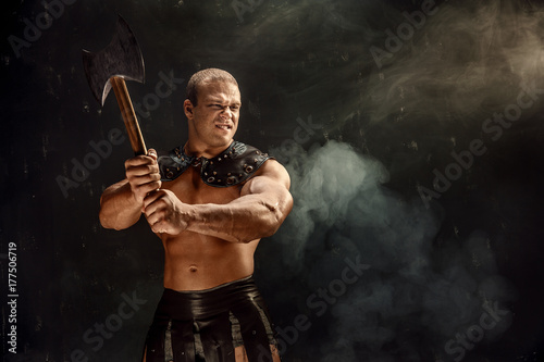 Muscular brutal man with axe in historic gladiator costume. Poster