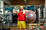 Fat funny man with dumbbells and balls in the gym. - 177511564