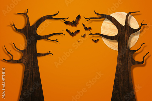 Halloween and decoration concept. Bats flying and tree made from wood on orange brick wall