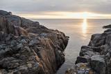 Sunrise on the Baltic sea with sunlit rocks. - 177569704