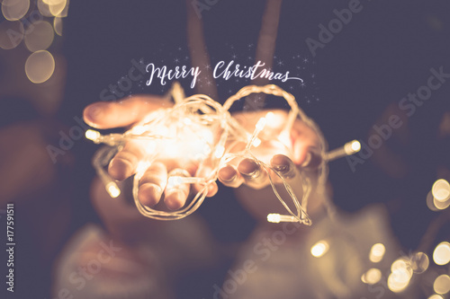 Foto Murales Merry christmas glowing word over hand with party light  string bokeh in vintage filter,Holiday, new year season.