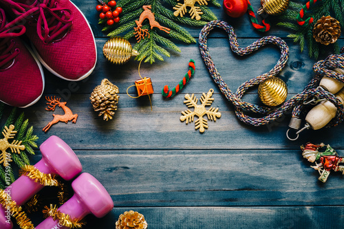 Leinwanddruck Bild Exercise, Fitness and Working Out Merry Christmas and Happy new year concept, dumbbells, sport shoes, skipping rope or jump rope  in heart shape with Christmas decoration items on wood background.