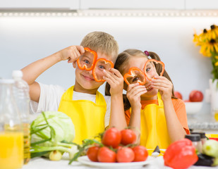 Happy kids having fun with food vegetables at kitchen holds pepper before his eyes like in glasses