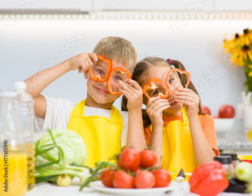 Happy kids having fun with food vegetables at kitchen holds pepper before his eyes like in glasses - 177603941