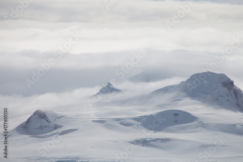 Papiers peints Antarctique Wind and clouds sweep over this mountain in Antarctica.