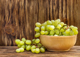 Bowl with fresh ripe green grapes on wooden background.