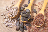 Flaxseed, pumpkin and sunflower seeds in wooden spoons. - 177614379