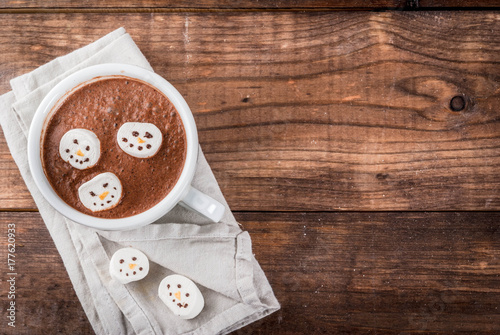 Canvas Chocolade Traditional Christmas drink idea. Hot chocolate mug with marshmallow, decorated in the form of snowmen, On wooden table copy space
