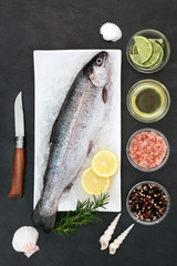Rainbow trout healthy heart food on crushed ice with rustic knife, rosemary herb, peppercorns, olive oil, himalayan salt, lemon and lime fruit on slate background. High in omega 3.
