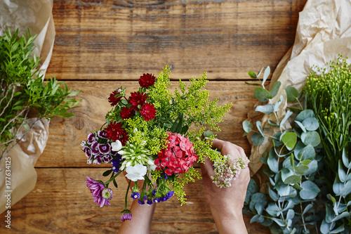 hands binding a wild flower bouquet flowershop Poster