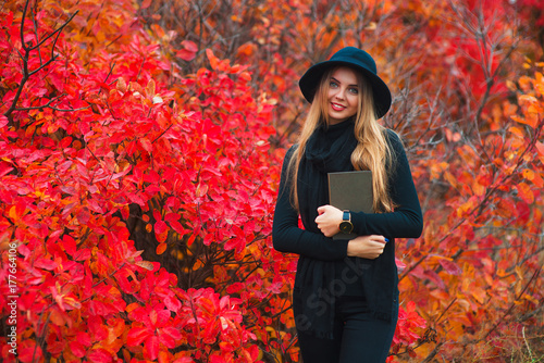 beautiful girl with book in the autumn park - 177664106