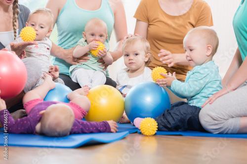 Leinwanddruck Bild Junge Mütter und ihre Kinder spielen gemeinsam im Mutter-Kind-Kurs