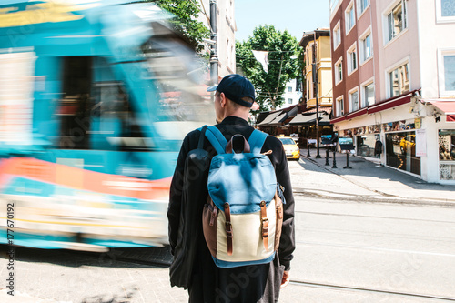 Man standing in front of road with tram Poster
