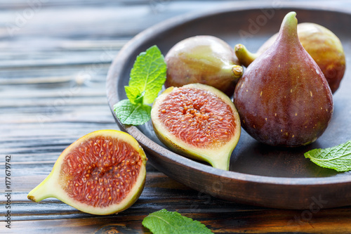 Fresh figs and mint leaves on a wooden dish.