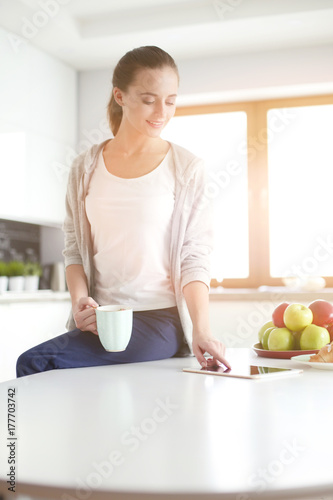 Happy woman drinking tea in the kitchen at home.
