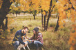 Cute couple playing with their dog in the fall leaves