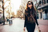 Young woman with shopping bags walking on street - 177727331
