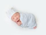 Sleeping newborn baby swaddled in a light blue wrap - 177727751