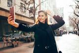 Beautiful young woman taking selfie on street - 177728522