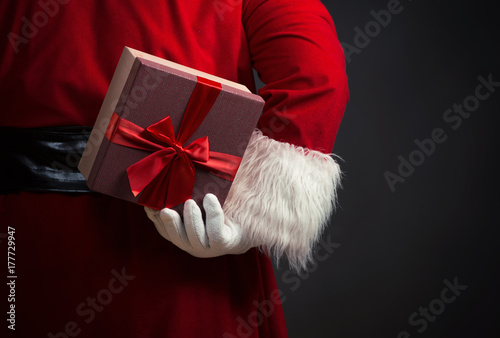 Santa Claus holding a presents, over a dark background плакат
