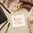 """Flat lay of artist home office in bed. Handwritten inspirational quote """"find joy in the ordinary"""" on a paper card"""