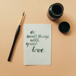 """Inspirational quote """"do small things with great love"""", ink, paint brush on a pale peach pastel background. Artist workspace"""