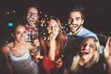 Grupa ludzi o imprezie, dmuchanie konfetti