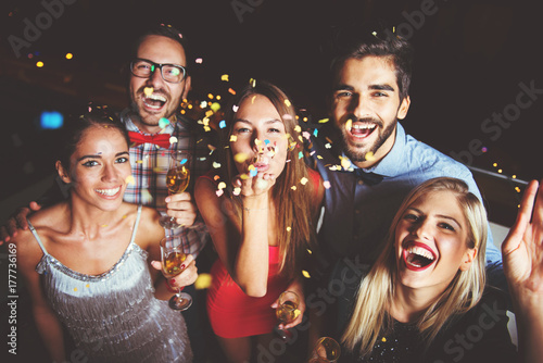 Foto Murales Group of people having a party, blowing confetti