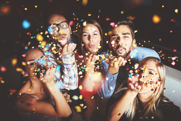 Group of people having a party, blowing confetti