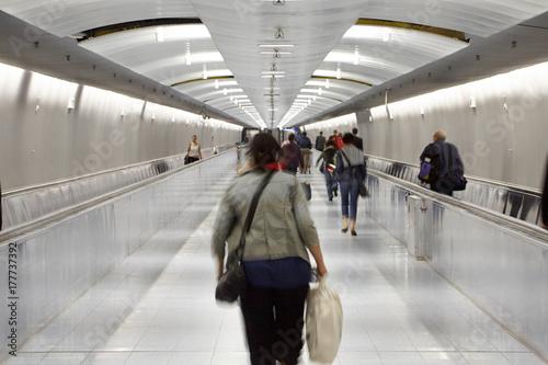 People in Long corridor passage with escalators motion blur Plakát